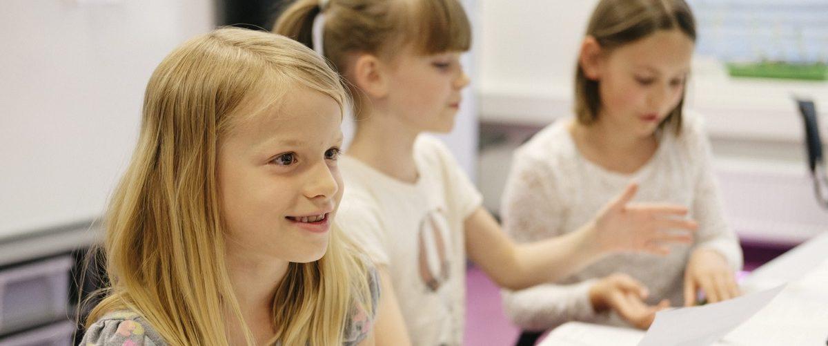 Tre jenter som sitter i klasserommet og arbeider med skoleoppgaver. Foto