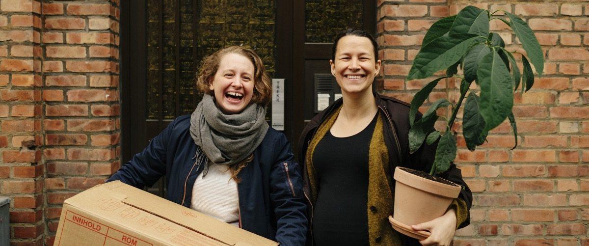 To kvinner med flytteeske og plante foran sitt nye hjem. Foto
