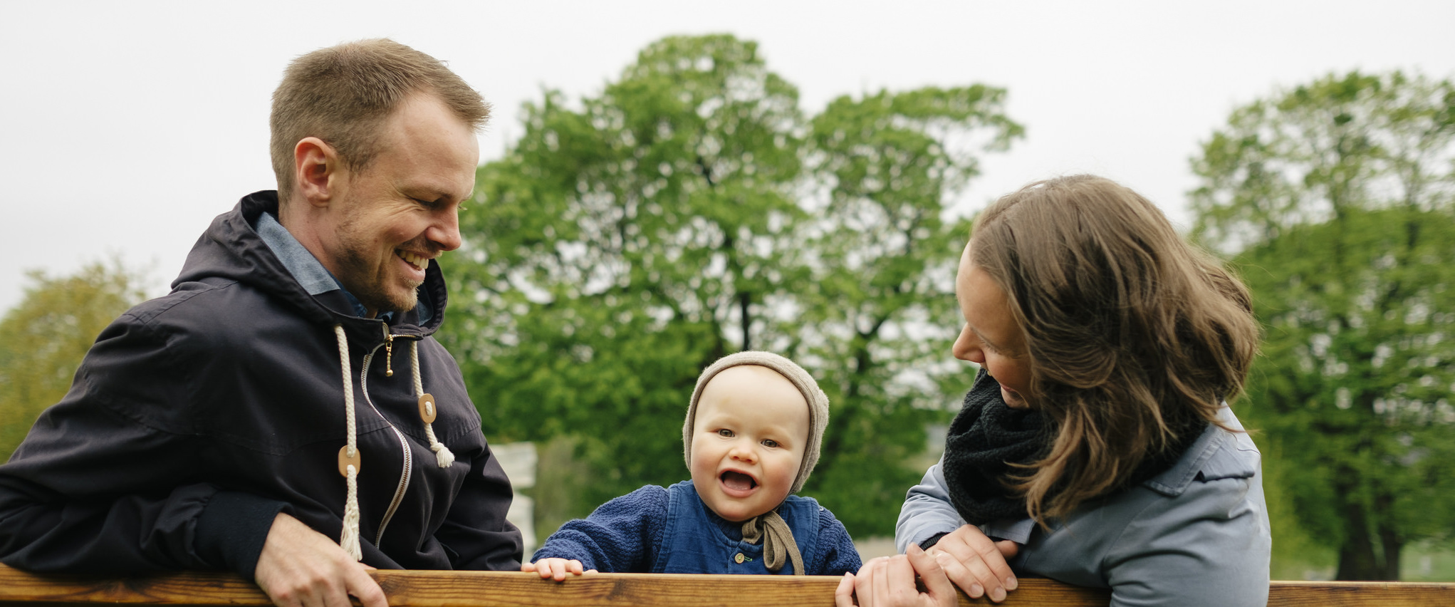Foreldre med en kjempesmilende baby. Foto