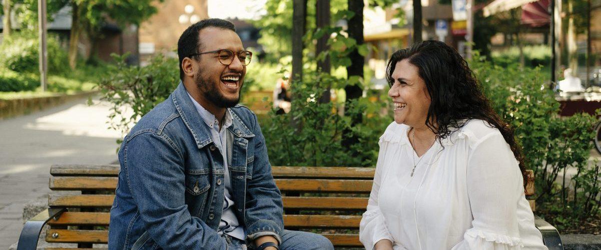 Leende mann og kvinne på benk. Foto