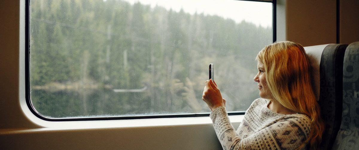 Kvinne på togtur som tar bilde av naturen toget passerer. Foto