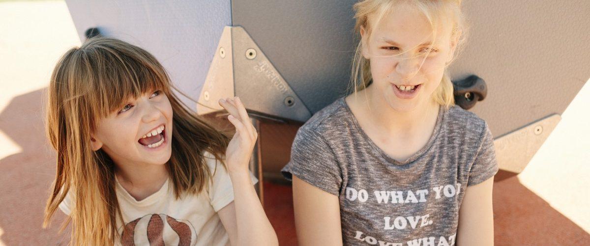 To jenter som sitter foran et lekeapparat. Foto