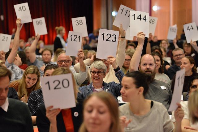 Fotografi av landsmøtedelegater som løfter sine delegatskilt under votering